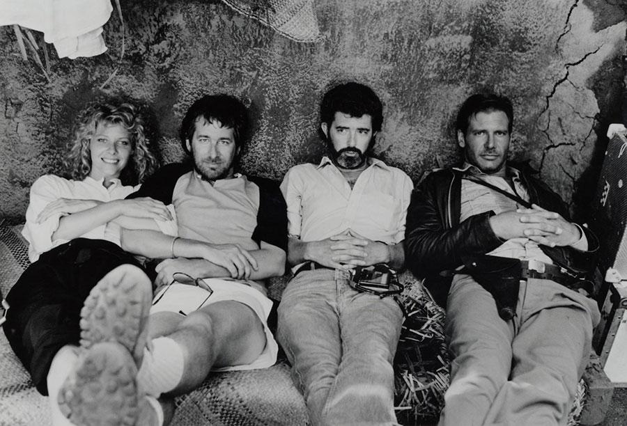 """Sul set di """"Indiana Jones e il Tempio Maledetto"""", protagonisti, regista e creatore della saga. Da sinistra: Kate Capshaw (diventata poco tempo la signora Spielberg), StevenSpielberg, George Lucas e Harrison Ford."""